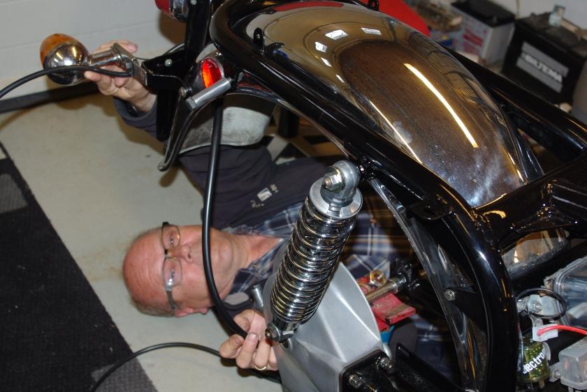 Arvid monterer ledningsett under bakskjerm.